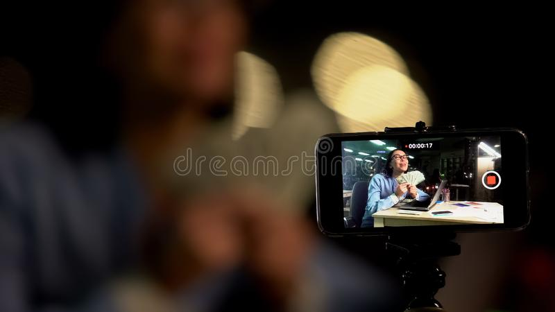 Camera recording excited young lady holding dollar bills, business advertising royalty free stock photos