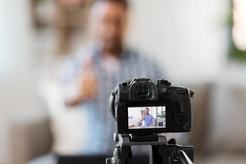 Camera recording video blogger showing thumbs up. Blogging, videoblog and people concept - camera recording video blog of indian male blogger showing thumbs up stock photography