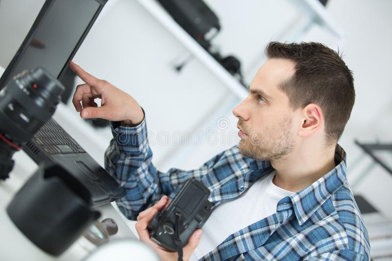 Camera repairman looking at laptop royalty free stock photography