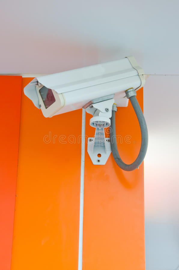 Camera for security. On orange wall stock photo