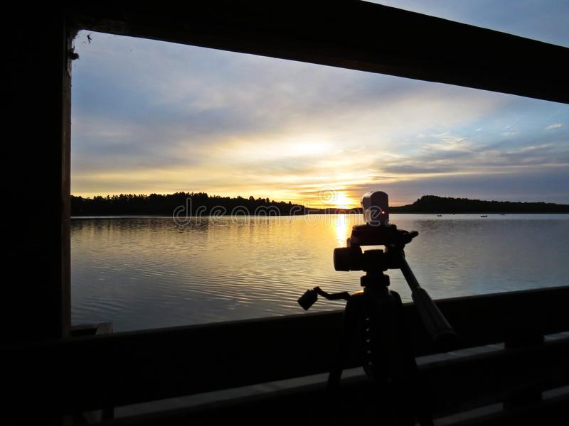 Camera Shooting Sunset Over Beautiful Lake with Cloudy Sky in background stock images