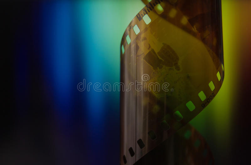 Camera strip on rainbow background. Film industry, memories in negative, filmed moments of life, photo in negatives royalty free stock photography
