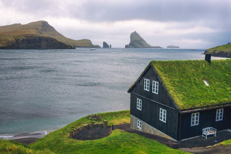 Camera sulla costa di isole faroe con la pila del mare di Drangarnir nei precedenti immagine stock libera da diritti