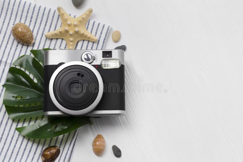 Camera with summer accessories: monstera eaves, star fish and towel, shells and stones on white wooden table royalty free stock images