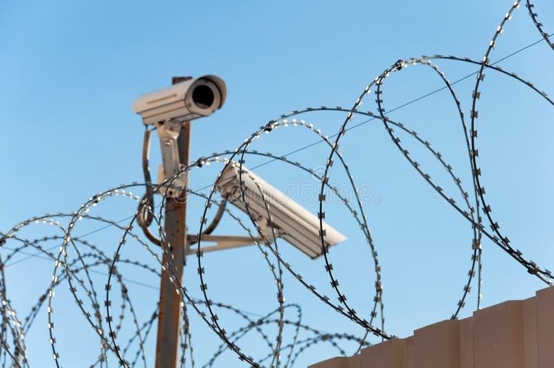 Camera surveillance and barbed wire. Camera surveillance and a barbed wire royalty free stock photo