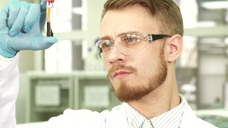 Close-up of the face of the lab worker who is studying the test tube with the assays royalty free stock photography