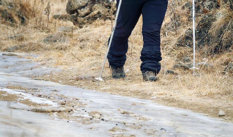 Camera takes off his feet in winter sportswear, hiking boots, trekking poles. The camera takes off his feet in winter sportswear, hiking boots, trekking poles royalty free stock images