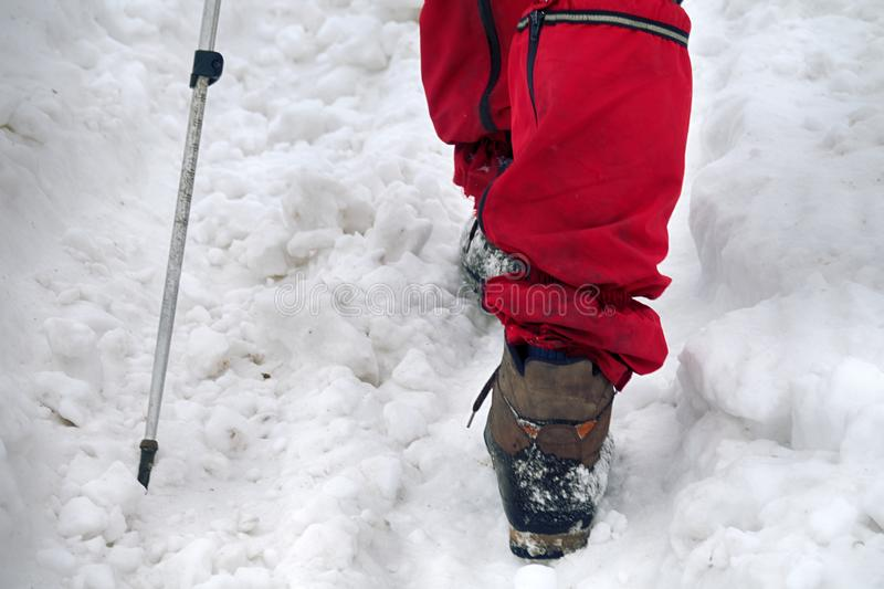 Camera takes off his feet in winter sportswear, hiking boots, trekking poles. The camera takes off his feet in winter sportswear, hiking boots, trekking poles royalty free stock image