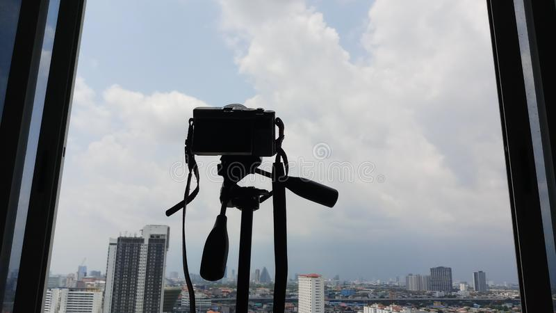 camera with tripod shooting photography cityscape outside the window royalty free stock photo