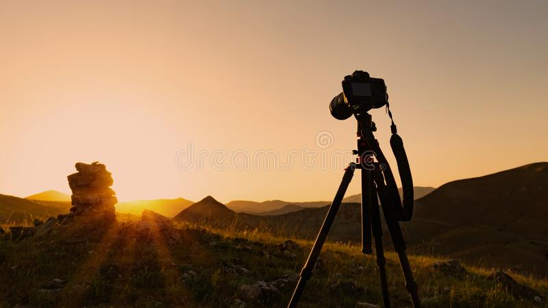 Camera on a tripod, shooting a sunset royalty free stock photos