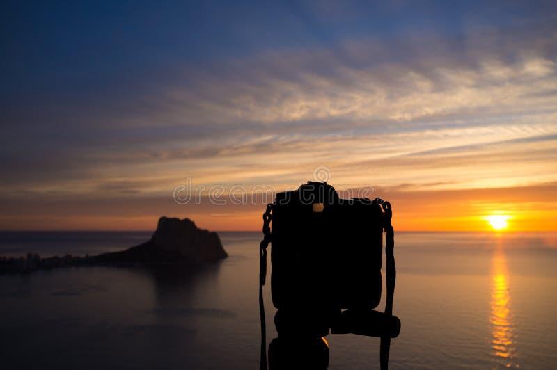 Camera on tripod with sunrise stock image