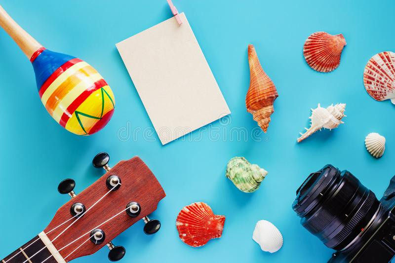 Camera, ukulele, maracas, blank paper postcard and sea shells on. Blue background for musical instrument, hobbies, travel and relaxation concept royalty free stock images