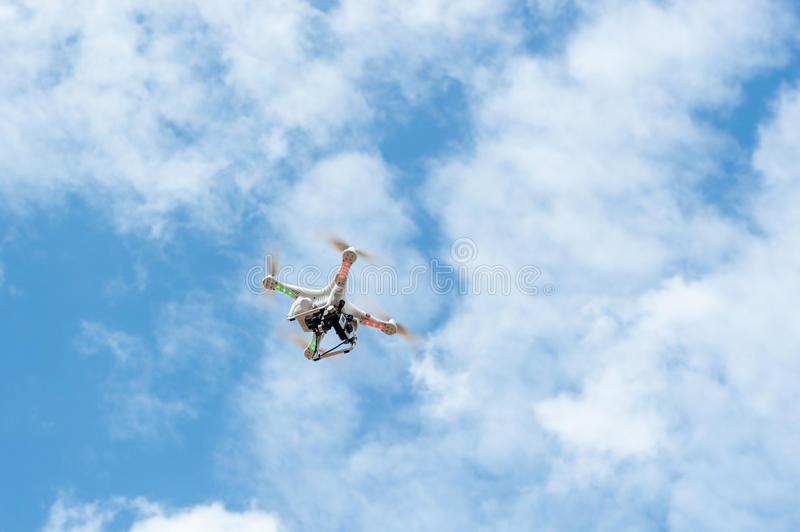 Camera white drone hovering in a bright blue sky stock image