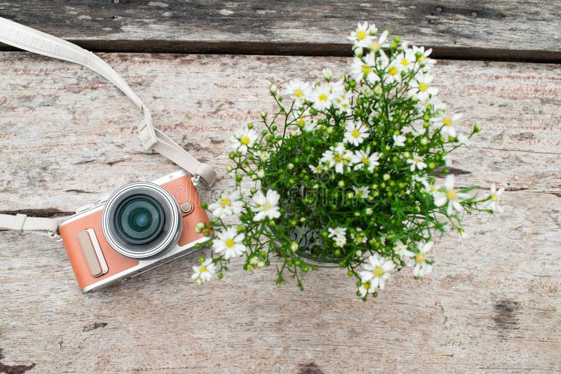 Camera with white flower vase on old brown wooden desk. Top view royalty free stock images