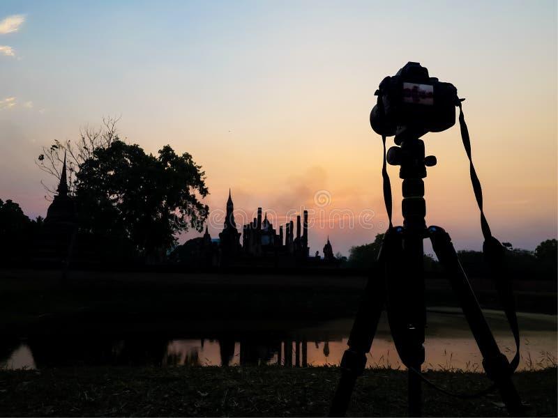 Cameradriepoot en de zonsonderganghemel van het ruïnesilhouet royalty-vrije stock afbeeldingen