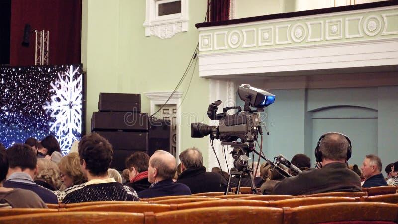 Cameraman con la cámara de la difusión de TV en el trípode fotos de archivo