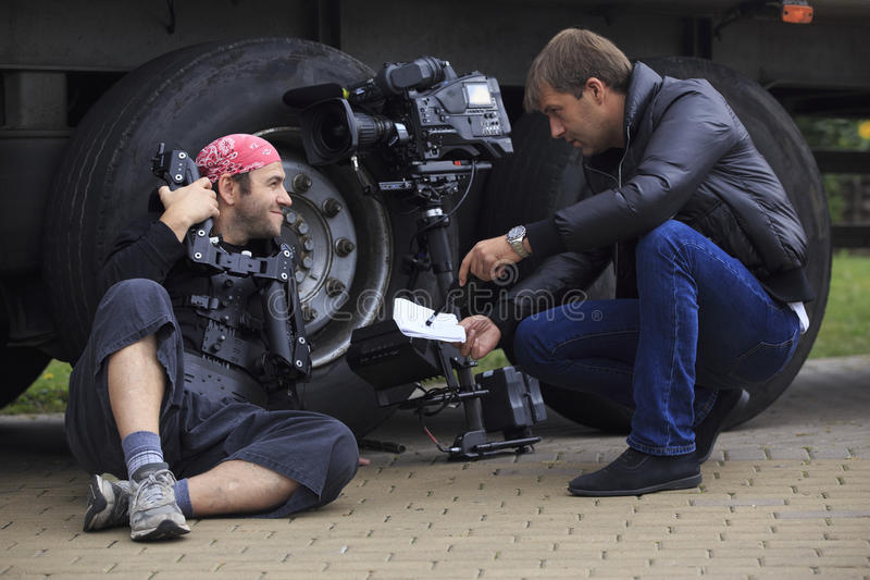 Cameraman and director. Discuss scene shooting sitting at the truck's wheels with professional tv-camera and stabilization system beside stock image