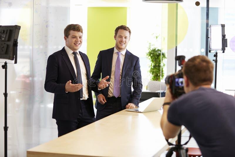 Cameraman en twee zakenlieden die een collectieve video maken royalty-vrije stock afbeelding