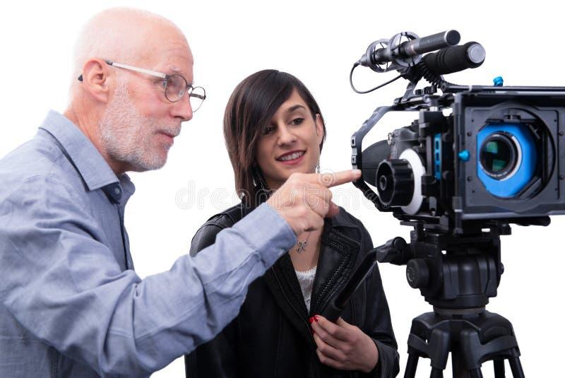 Cameraman et une jeune femme avec une cam?ra de film DSLR sur le blanc images stock