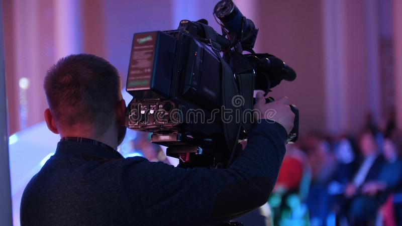 Cameraman filming the concert and the audience. Mid shot royalty free stock photo