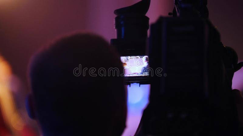 Cameraman filming the piano performance in colorful lights. Back view royalty free stock photo