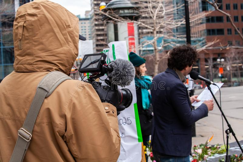 Cameraman films environmentalist speech. An over the shoulder view of a camera operator as he films an environmental activist give a speech during an eco stock photo