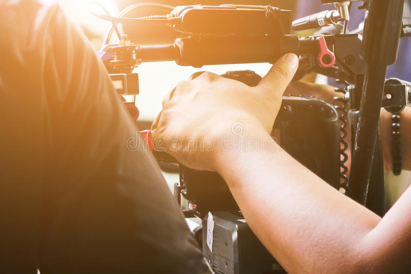 Cameraman with his video camera shooting. Hands Adjusting Camera,film production crew,behind the scenes background stock photography
