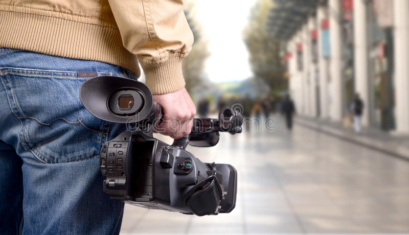 Cameraman holding his professional camcorder. In the street royalty free stock photography