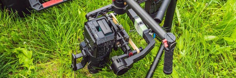 Cameraman installant le stabilisateur triaxial professionnel résistant de cardan pour la BANNIÈRE de caméra de cinéma, long forma photo libre de droits