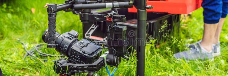 Cameraman installant le stabilisateur triaxial professionnel résistant de cardan pour la BANNIÈRE de caméra de cinéma, long forma photos stock
