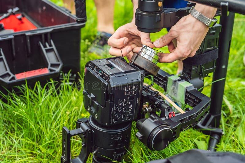 Cameraman installant le stabilisateur triaxial professionnel résistant de cardan pour la caméra de cinéma photos libres de droits