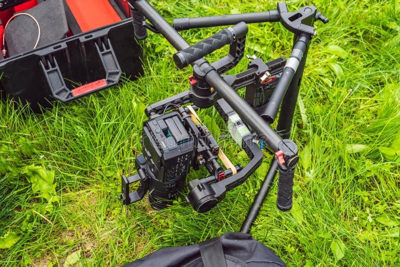 Cameraman installant le stabilisateur triaxial professionnel résistant de cardan pour la caméra de cinéma photo libre de droits