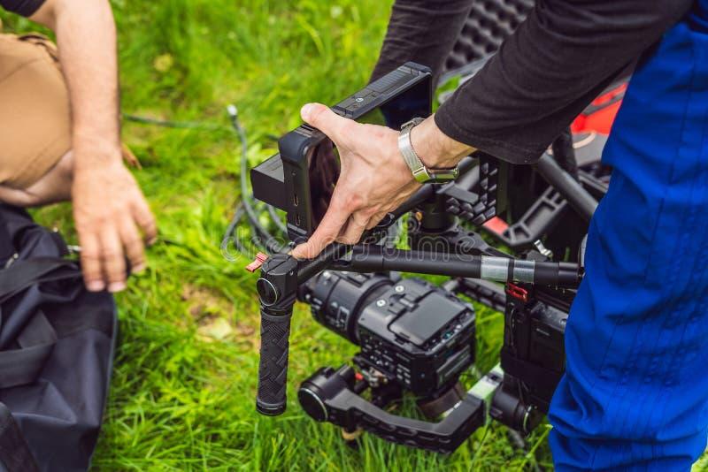 Cameraman installant le stabilisateur triaxial professionnel résistant de cardan pour la caméra de cinéma photos stock