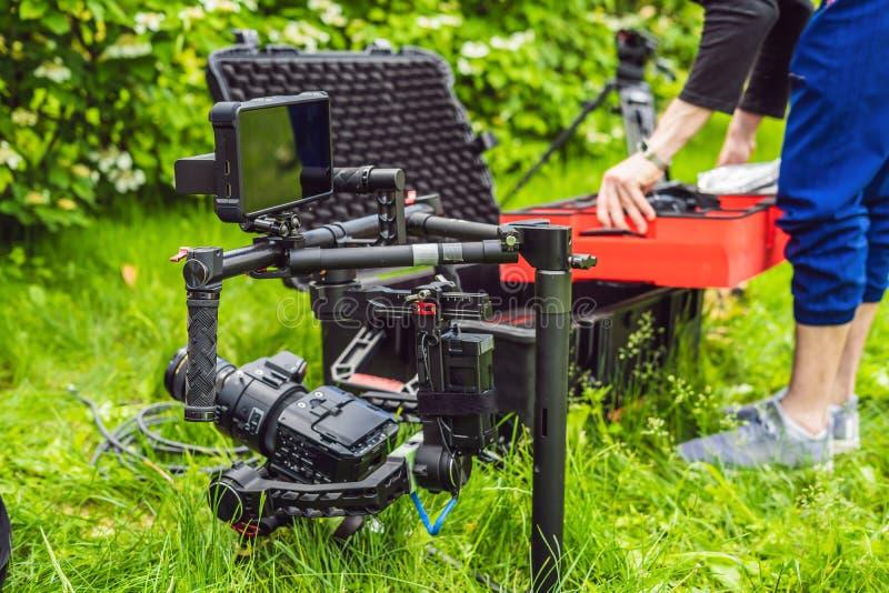 Cameraman installant le stabilisateur triaxial professionnel résistant de cardan pour la caméra de cinéma photographie stock