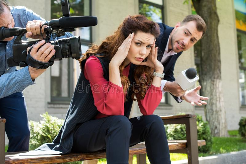 cameraman and male newscaster with microphone talking to frustrated businesswoman royalty free stock image