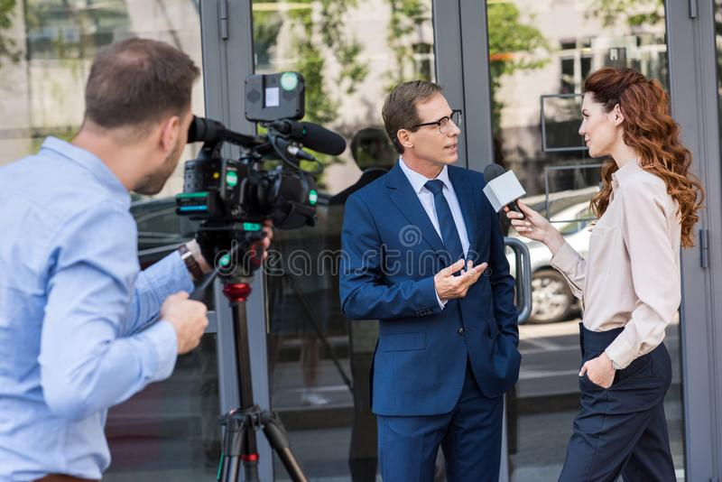 Cameraman and news reporter with microphone interviewing businessman near office. Building stock image