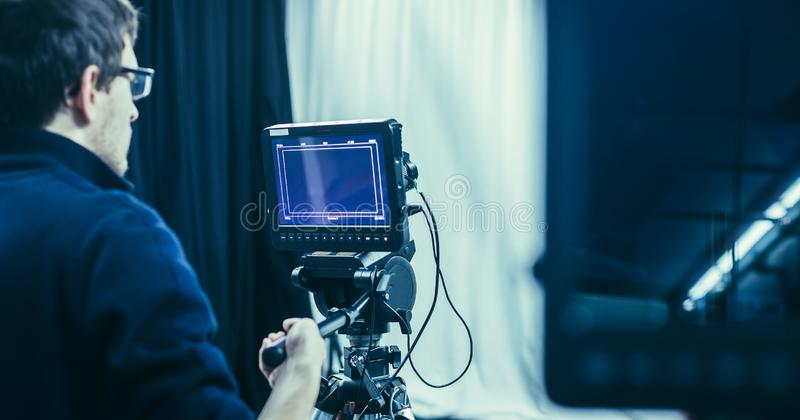 Cameraman operates a film camera, broadcasting studio. Male cameraman is operating a film camera in a television studio broadcast production microphone stock photos