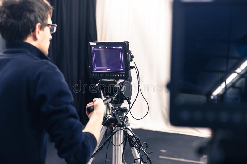 Cameraman operates a film camera, broadcasting studio. Male cameraman is operating a film camera in a television studio broadcast production microphone stock images