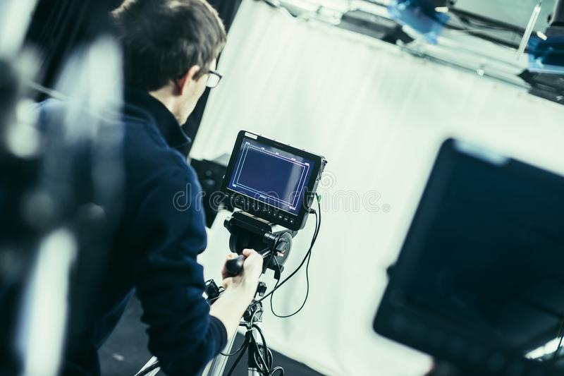 Cameraman operates a film camera, broadcasting studio. Male cameraman is operating a film camera in a television studio broadcast production microphone stock photography