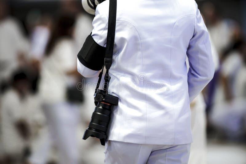 Cameraman profissional que suspende a precinta e câmera sem espelhamento com fundo de multidão desfocado fotografia de stock royalty free