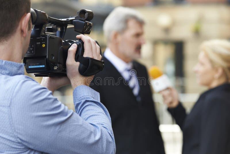 Cameraman Recording Female Journalist Interviewing Businessman stock image