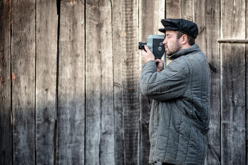 Cameraman with retro film camera. Concept - cinema industry, movie of 1970s. Cameraman with retro film camera. Idea - cinema industry, movie of 1970s royalty free stock photography
