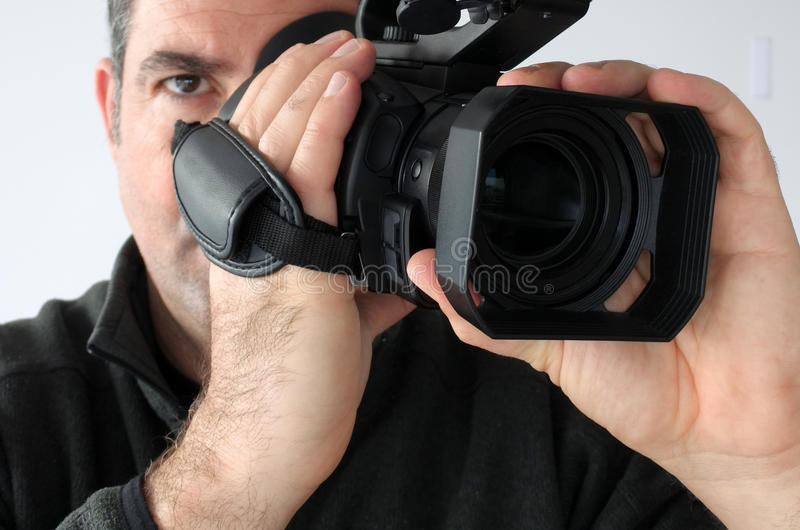 Cameraman shooting footage with video camera. Professional cameraman age 40 filming footage with video camera. Real people royalty free stock photo