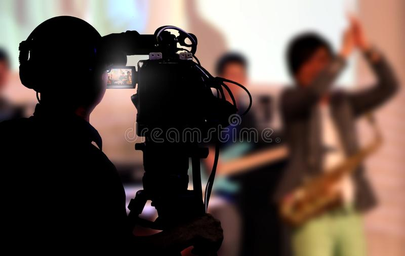 Cameraman shooting a live concert. With musician on stage stock image