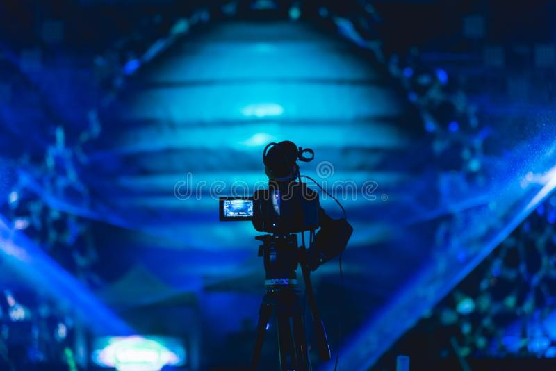 Cameraman shooting video production camera videographer. In concert music festival stock photography