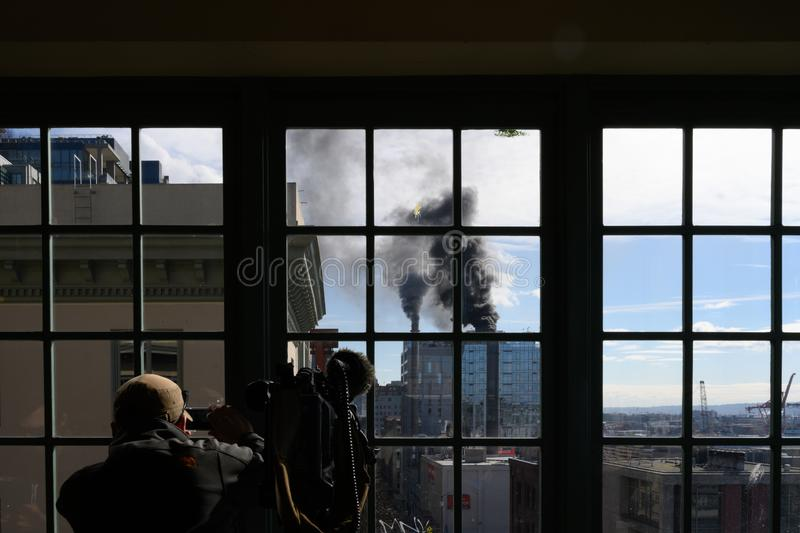 Cameraman on site filming smoke billowing from steam plant royalty free stock images