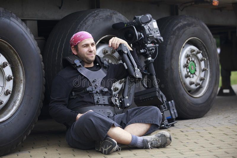 Cameraman takes a rest. Young cameraman sits leaning on the truck's wheels with steadicam and video camera stock photos
