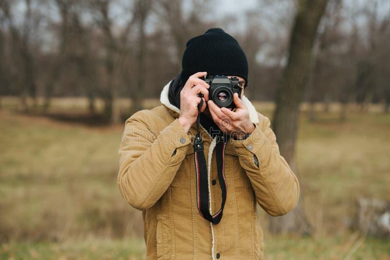 Cameraman tirando uma foto sua Homem com câmera no interior do outono foto de stock royalty free