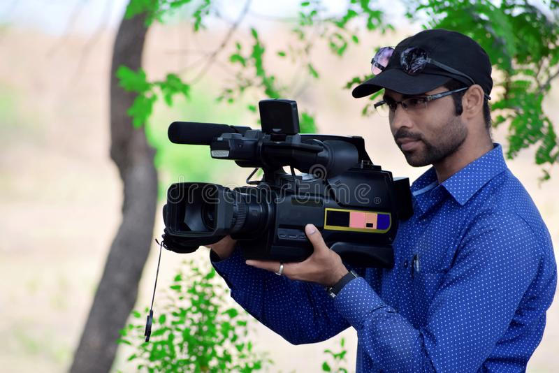 Cameraman using a professional camcorder outdoor. For a filming documentary stock photography