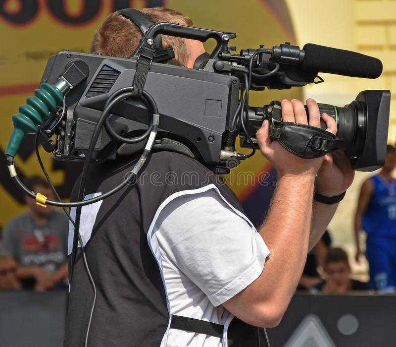 Cameraman at work outdoor. In summer stock image